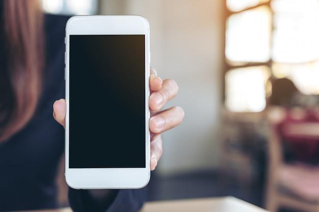 Donna che mantiene e che mostra il telefono cellulare bianco con schermo vuoto nella caffetteria