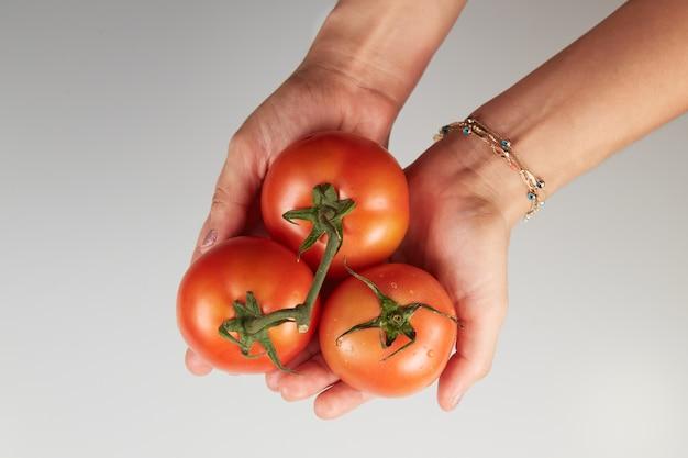 Donna che mantiene i pomodori su sfondo bianco.