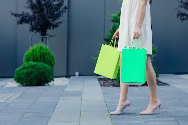 Donna che mantiene i sacchetti colorati della spesa sulla strada con copia spazio - concetto di acquisto.