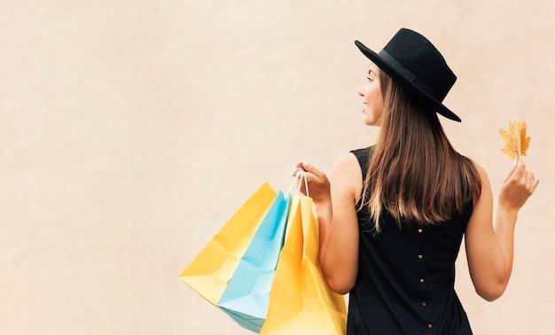 Donna che mantiene i sacchetti della spesa con copia spazio