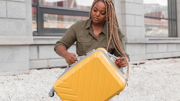 Donna che mantiene i suoi bagagli gialli
