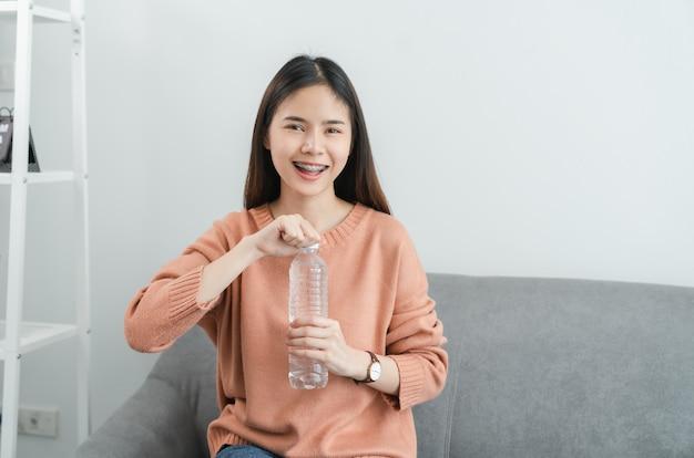 Donna che mantiene la bottiglia d'acqua seduta sul divano di casa