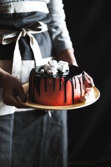 Donna che mantiene la torta con marshmallow sulla parete nera