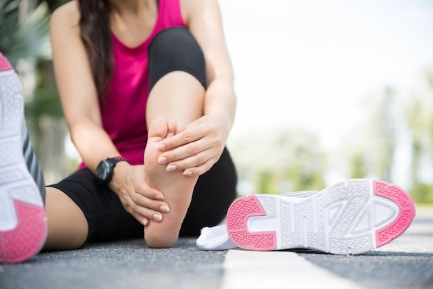 Donna che massaggia il suo piede doloroso. esecuzione di sport e concetto di infortunio.