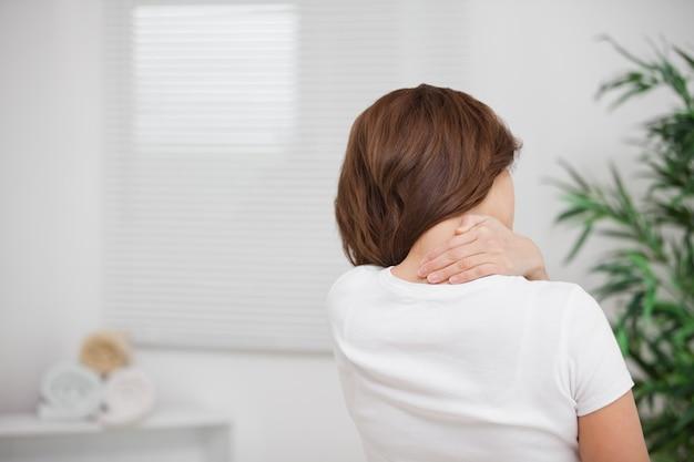 Donna che massaggia la sua dolorosa nuca