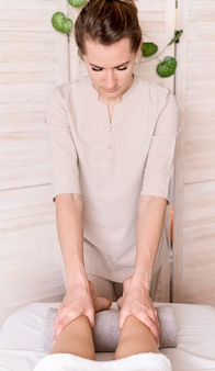 Donna che massaggia le gambe del cliente
