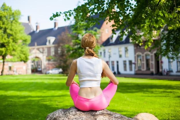 Donna che medita e che fa gli esercitatori di asana di yoga in parco