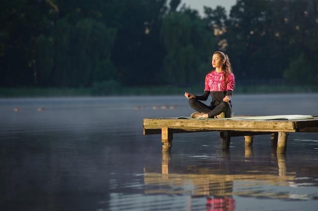 Donna che medita in natura sul fiume. yoga