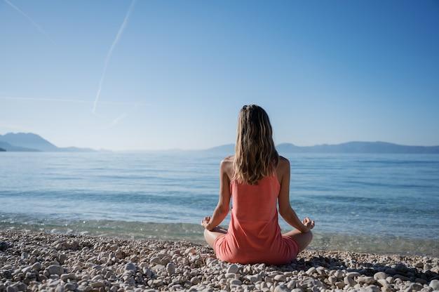 Donna che medita su spiaggia
