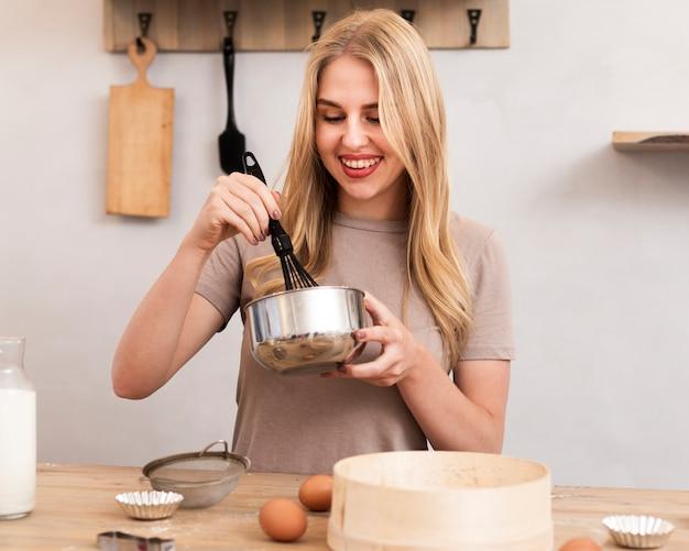 Donna che mescola le uova in una ciotola metallica