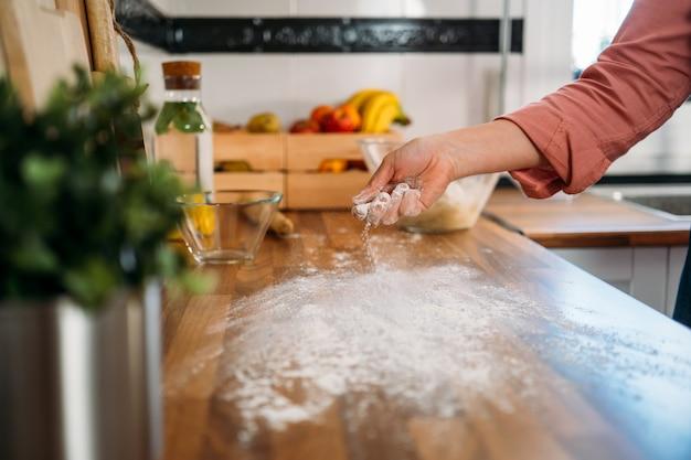 Donna che mette farina sul bancone della cucina in legno per impastare la pasta della pizza