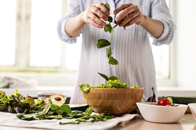 Donna che mette gli spinaci in un'insalata