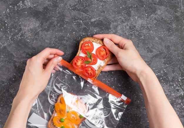 Donna che mette i panini vegetariani in un sacchetto