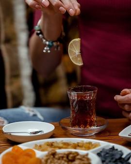 Donna che mette la fetta di limone sul suo tè nero nel tradizionale vetro a forma di pera