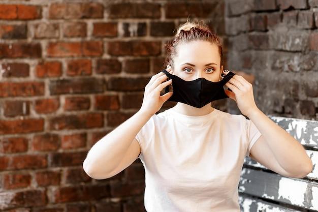 Donna che mette la maschera per il viso dalla diffusione del coronavirus