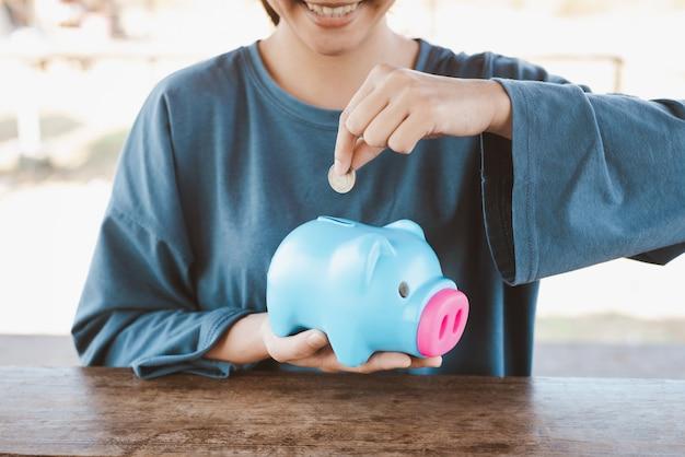 Donna che mette moneta nel porcellino salvadanaio