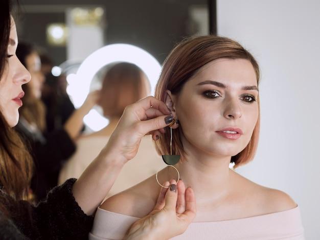 Donna che mette orecchini sul modello