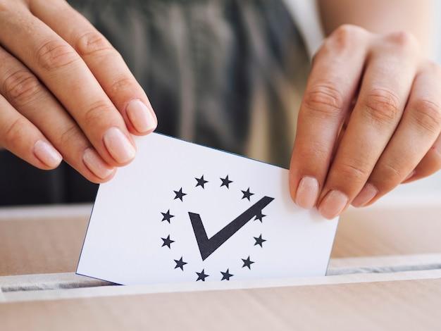 Donna che mette scheda elettorale in primo piano della scatola