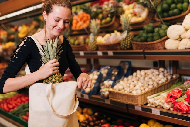 Donna che mette un ananas in una borsa