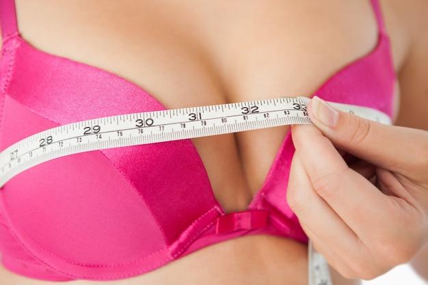Donna che misura il petto in reggiseno rosa