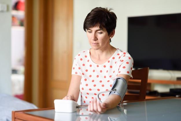 Donna che misura la sua propria pressione sanguigna a casa.