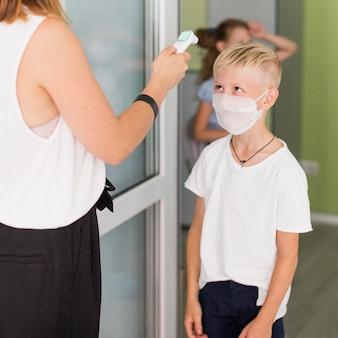 Donna che misura la temperatura di un ragazzo