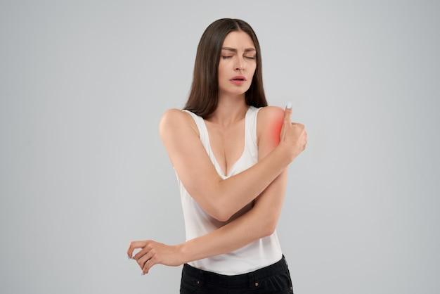 Donna che mostra dolore alla spalla