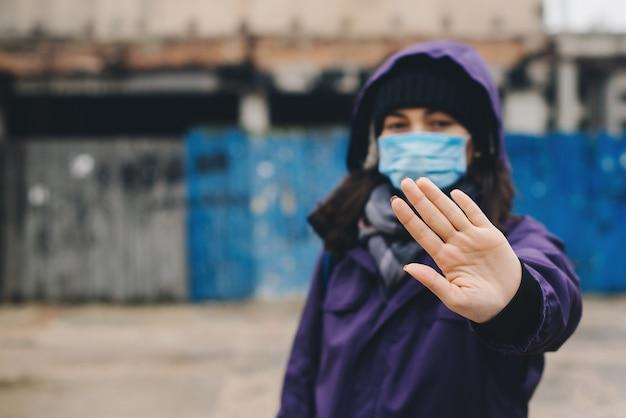Donna che mostra fermata gesto. la donna indossa una maschera protettiva contro le malattie infettive e l'influenza. concetto di assistenza sanitaria. quarantena di coronavirus.