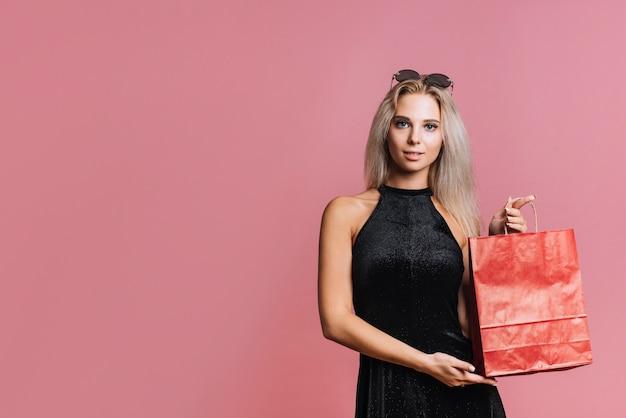 Donna che mostra il sacchetto di carta rosso