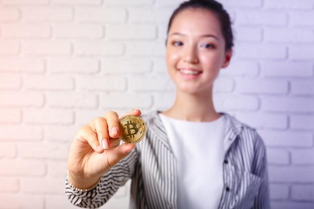 Donna che mostra la moneta d'oro bitcoin