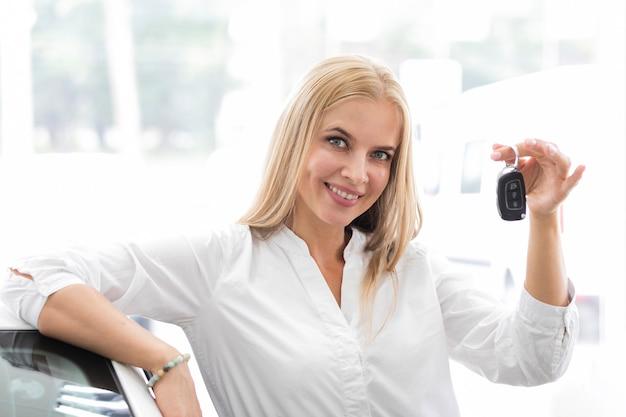 Donna che mostra le chiavi dell'automobile e che esamina la macchina fotografica