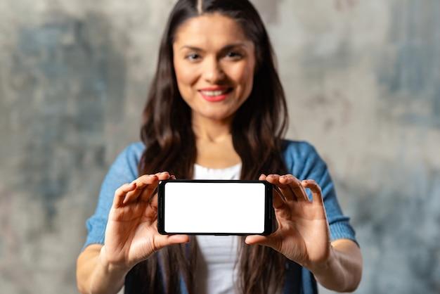Donna che mostra lo schermo del telefono cellulare. concentrati sullo smartphone.