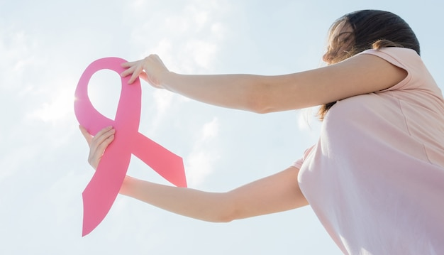 Donna che mostra nastro rosa per sostenere il cancro al seno.