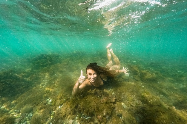 Donna che mostra pollice sul gesto sott'acqua