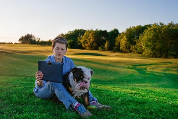 Donna che mostra qualcosa o che insegna al cane sul prato nel parco