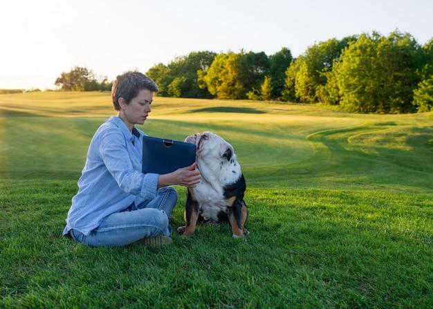 Donna che mostra qualcosa o che insegna al cane sull'erba verde nel parco