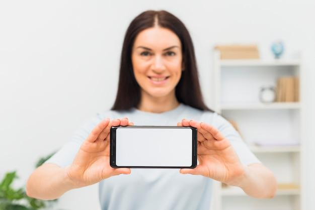 Donna che mostra smartphone con schermo bianco vuoto