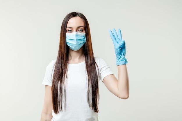 Donna che mostra tre dita che indossano maschera e guanti