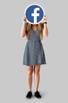 Donna che mostra un'icona di facebook