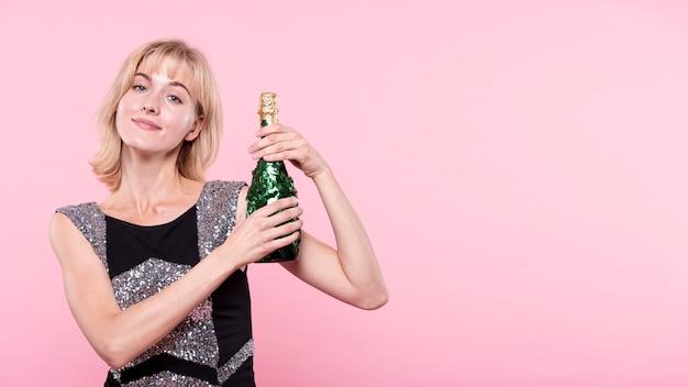 Donna che mostra una bottiglia di champagne su fondo rosa