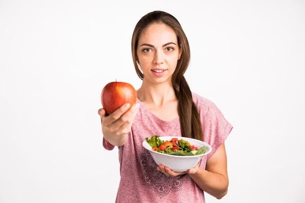 Donna che mostra una mela e che esamina macchina fotografica
