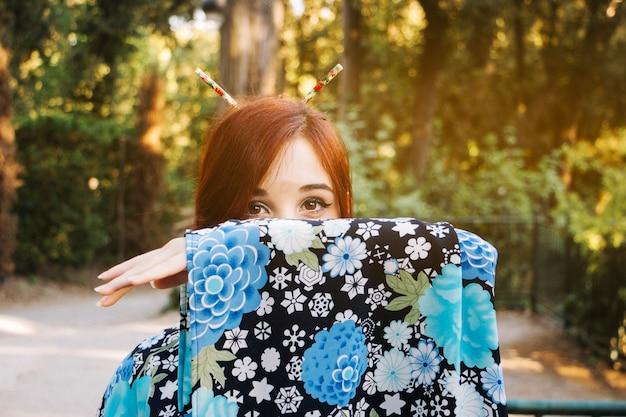 Donna che nasconde il viso dietro il manicotto del kimono