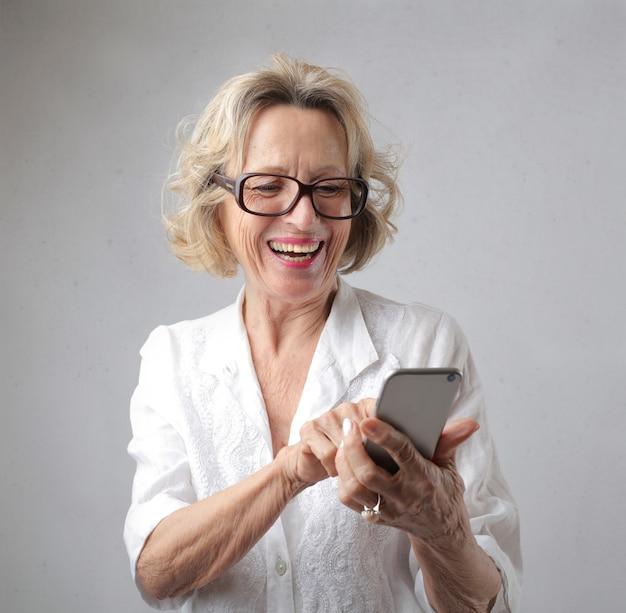 Donna che naviga felicemente in internet e comunica con amici e familiari tramite smartphone