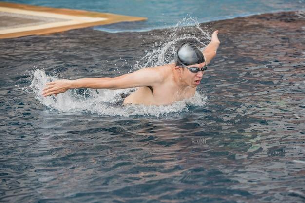 Donna che nuota il colpo di farfalla in una piscina.