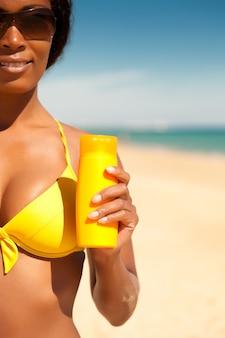 Donna che offre crema solare sulla spiaggia