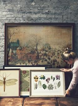 Donna che organizza cornici e arte