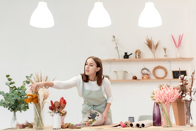 Donna che organizza i mazzi di fiori nel suo negozio