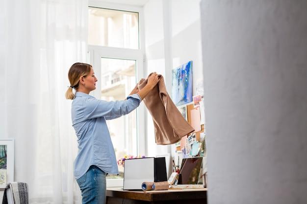 Donna che organizza i vestiti in borsa