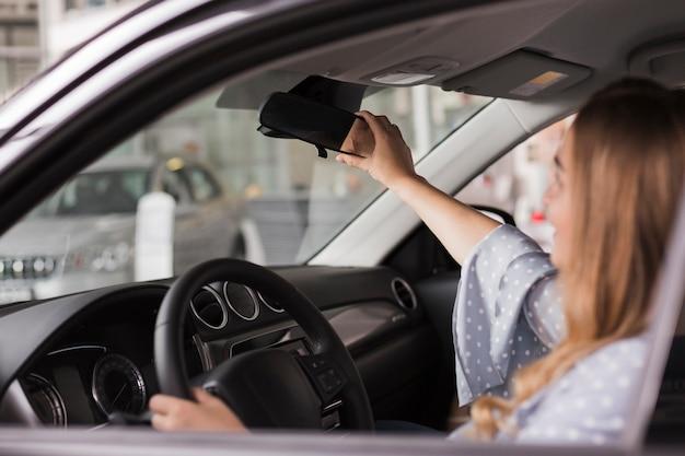 Donna che organizza specchio retrovisore