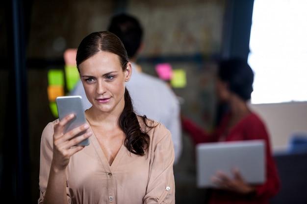Donna che osserva il suo telefono cellulare